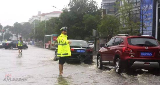 暴雨中,交警打光脚执勤
