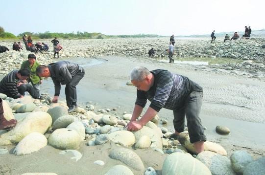 许多村民们在河滩上挖古钱币