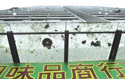 8月16日,成都站北东街云景豪庭小区外,一楼商铺玻璃已经千疮百孔。