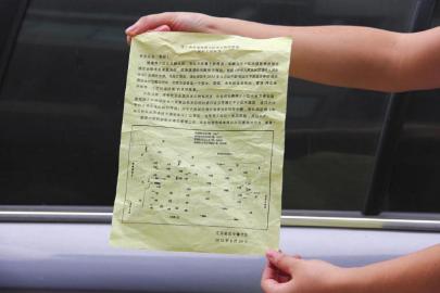 居民展示交警印发的《小区占道整改通知书》。