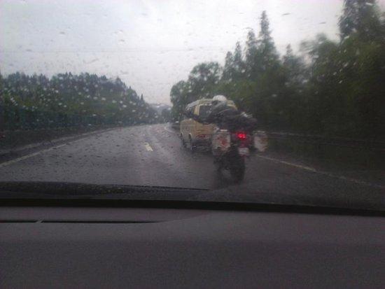 10月9日,摩托车驾驶员在成渝高速上挥手。