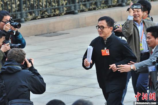 全国政协委员成龙在人民大会堂前跑步突围。中新社发 贾国荣 摄