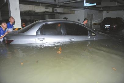 市民正试图将爱车移出被雨水淹没的车库