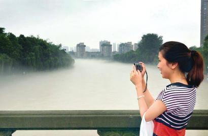 12日早晨,大雨之后,一位市民站在雾气弥漫的锦江河边拍照
