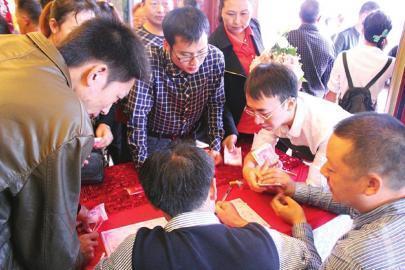 婚礼上,多人手中拿着一沓百元钞票随份子。(网友供图)