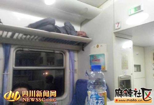 中年男子平躺在火车行李架上安然入睡。