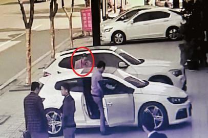 12月12日,试驾男子(红圈)准备和二手汽车店工作人员一起试车。