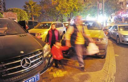 12月11日,成都桐梓林东路,机动车占用人行道乱停放现象严重,影响了路人通行。
