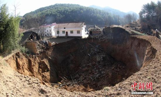 图为天坑导致多间民房受损。中新社发 高志农 摄