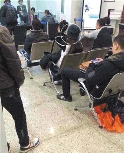 网友微博发布汤唯(戴帽者)昨日在银行办理业务的照片。