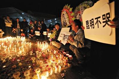 """昨晚,昆明火车站广场,一些市民手举""""昆明不哭""""""""严惩疆独""""等标语。当晚,市民聚集在一起为在袭击中遇难者默哀祈福。"""