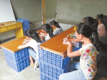 孩子们在果筐堆成的课桌上上课。